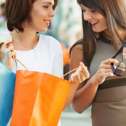 Two woman smiling while shopping