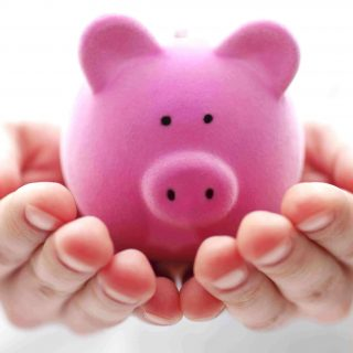 Pink piggy bank in hands
