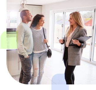 Couple talking with a realtor inside a house for sale