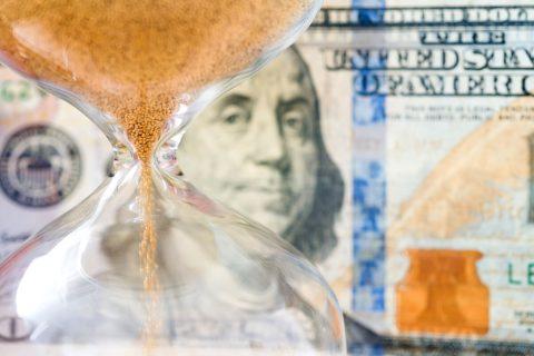 Hourglass in front of money