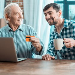 Son sitting next to Father holding a credit card