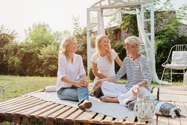 Three women outdoors talking and laughing