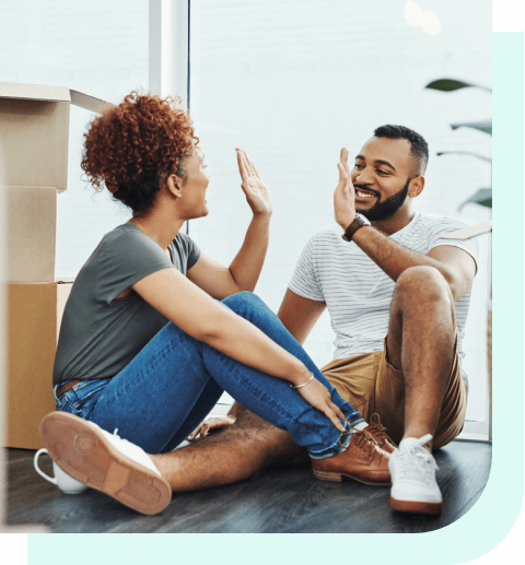 Couple high-fiving near moving boxes