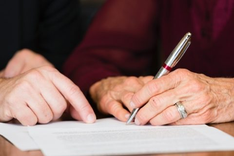 two people writing out a will