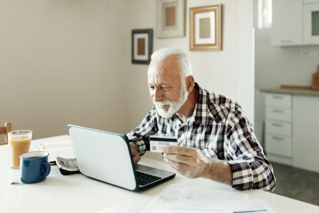 Senior Man using credit card and laptop